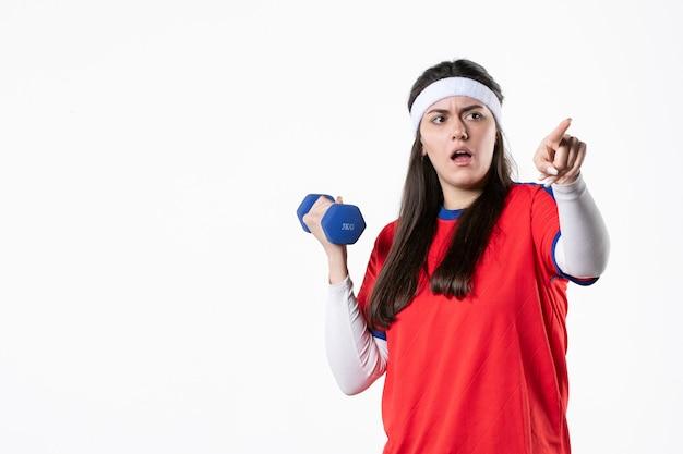Mulher jovem de frente para o esporte com halteres azuis na parede branca