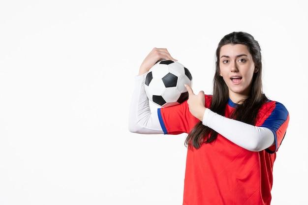 Mulher jovem de frente para o esporte com uma bola de futebol na parede branca