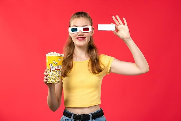 Mulher jovem de frente para o pacote de pipoca e o ingresso no filme de cinema de parede vermelha clara.