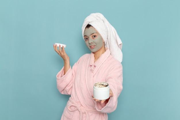 Mulher jovem de frente para o roupão rosa com máscara no rosto, chuveiro de parede azul claro, creme para limpeza de beleza