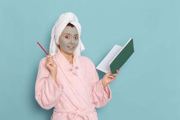 Mulher jovem de frente para o roupão rosa com máscara no rosto segurando o caderno na parede azul, creme de limpeza de beleza para cuidados pessoais