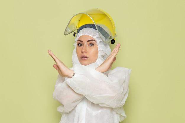 Mulher jovem de frente para o terno especial branco e capacete amarelo posando mostrando sinal de proibição no trabalho do espaço verde
