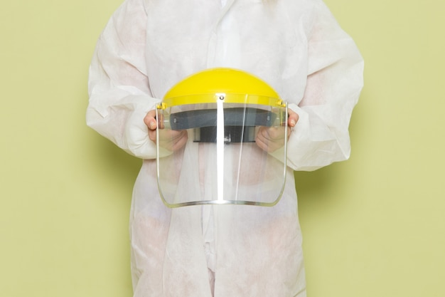 Mulher jovem de frente para o terno especial branco e capacete amarelo segurando-a no espaço verde