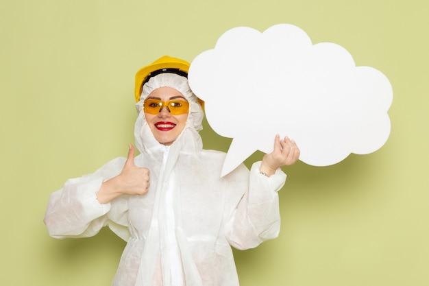 Mulher jovem de frente para o terno especial branco e capacete amarelo sorrindo segurando uma enorme placa branca no trabalho do espaço verde