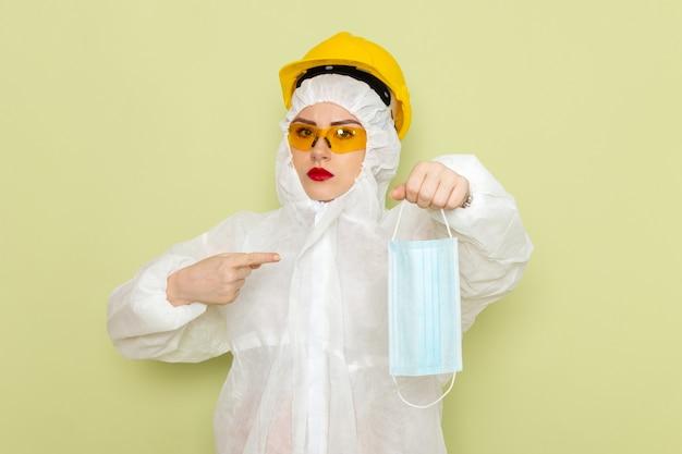 Mulher jovem de frente para o terno especial branco e capacete protetor amarelo segurando uma máscara estéril na ciência uniforme do traje espacial verde