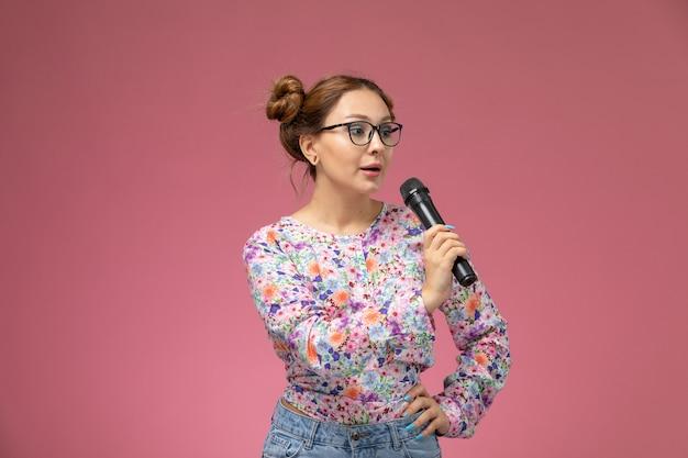 Mulher jovem de frente para uma camisa com design floral e jeans azul segurando o microfone e tentando cantar no fundo claro