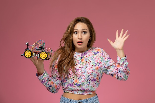 Mulher jovem de frente para uma camisa com design floral e jeans azul segurando um carrinho de brinquedo no fundo rosa