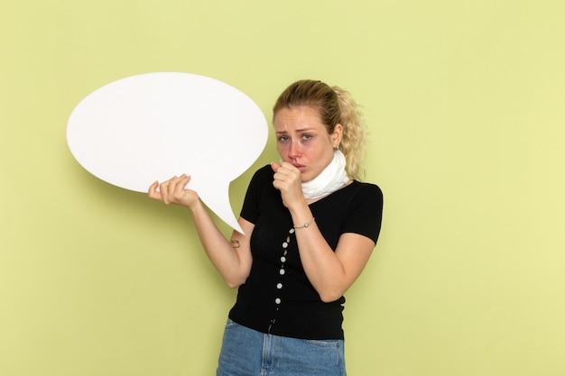 Mulher jovem, de frente, se sentindo muito doente e doente, segurando uma enorme placa branca, tossindo na parede verde.
