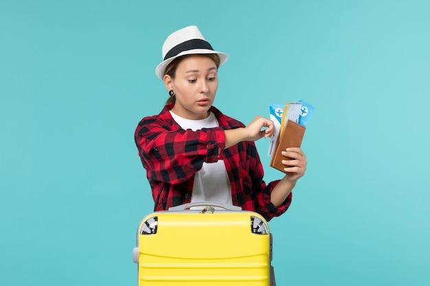 Mulher jovem de frente segurando a carteira e os ingressos, verificando as horas no espaço azul