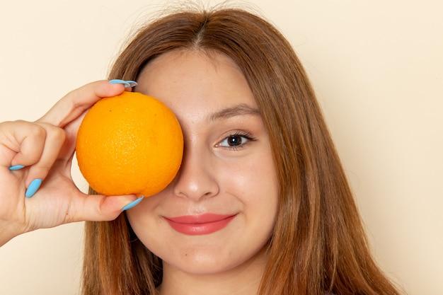 Mulher jovem de frente segurando laranja e sorrindo em cinza