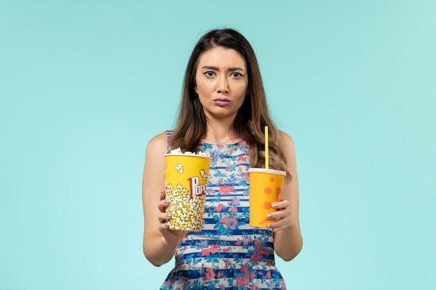 Mulher jovem de frente segurando pipoca e bebida na superfície azul clara