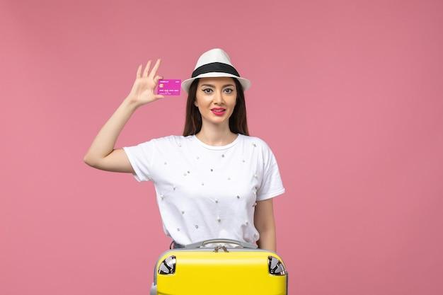 Mulher jovem, de frente, segurando um cartão do banco roxo na mesa rosa, emoções, viagem, mulher, verão
