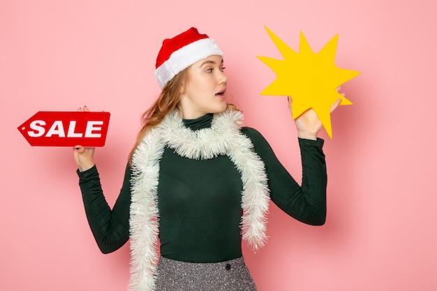 Mulher jovem de frente segurando uma grande figura amarela e escrita de venda no modelo de cor da parede rosa férias natal ano novo emoções