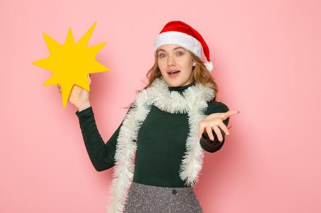 Mulher jovem de frente segurando uma grande figura amarela na cor rosa da parede modelo feriados natal ano novo emoção