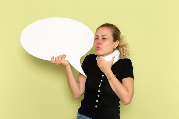 Mulher jovem de frente, sentindo-se muito doente e doente, segurando uma enorme placa branca segurando sua garganta na parede verde.