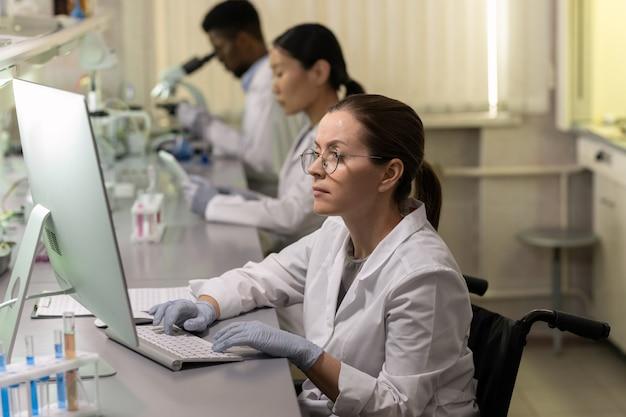 Mulher jovem de jaleco branco sentada à mesa em frente ao monitor do computador e trabalhando no computador do laboratório