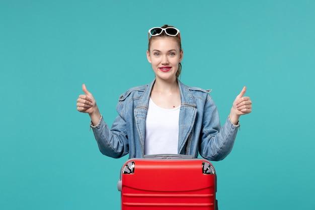 Mulher jovem de jaqueta azul se preparando para a viagem e posando com um sorriso no espaço azul