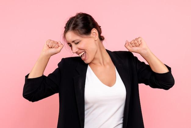 Mulher jovem de jaqueta escura, de frente, alegrando-se com fundo rosa