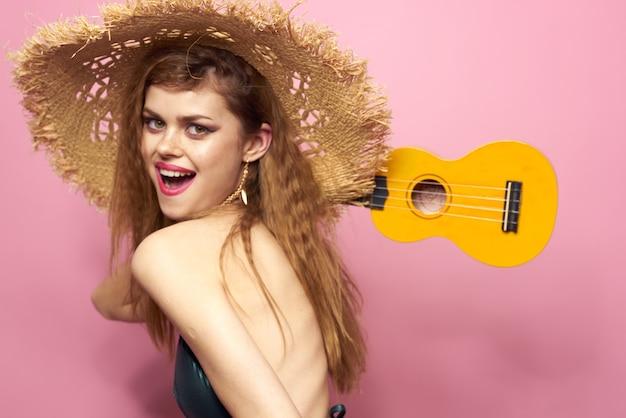 Mulher jovem de maiô e chapéu, tocando violão cavaquinho