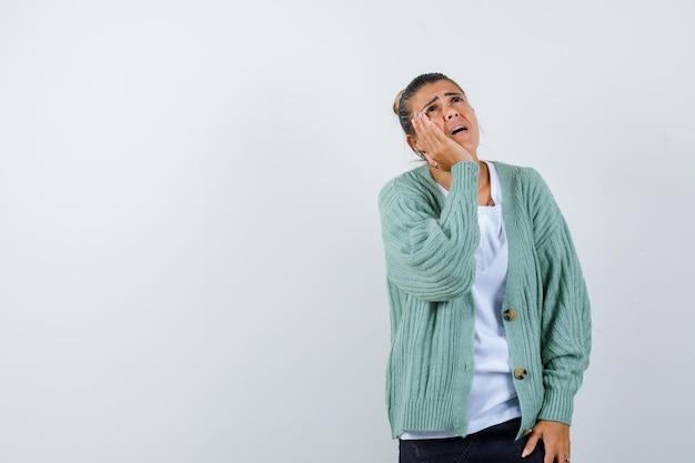 Mulher jovem de mãos dadas perto da boca ligando para alguém com uma camiseta branca e um casaco de lã verde menta e parecendo focada