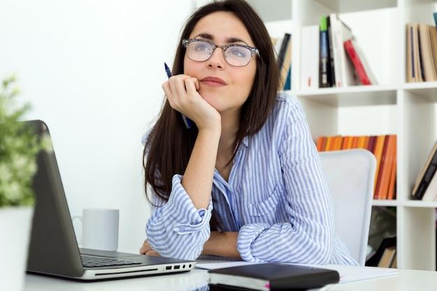Mulher jovem de negócios que trabalha com laptop no escritório.