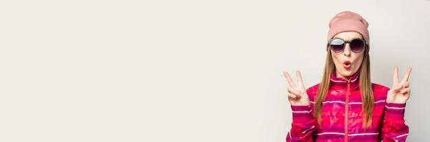 Mulher jovem de óculos, chapéu e jaqueta esporte rosa com uma cara de surpresa faz um gesto legal na frente