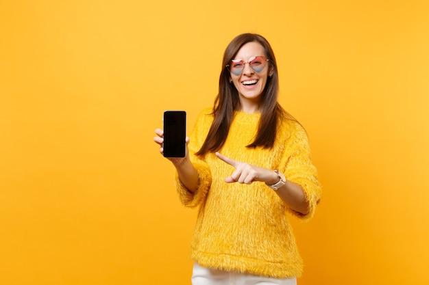 Mulher jovem de óculos de coração apontando o dedo indicador no telefone móvel com tela vazia preta em branco isolada em fundo amarelo brilhante a rir. pessoas sinceras emoções, estilo de vida. área de publicidade.