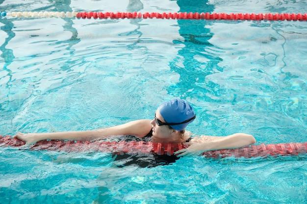 Mulher jovem de óculos e boné usando divisor de pista ao atravessar a piscina