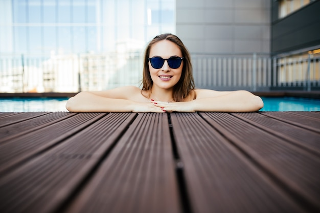 Mulher jovem de óculos escuros com um sorriso branco perfeito tomando banho em uma piscina nas férias