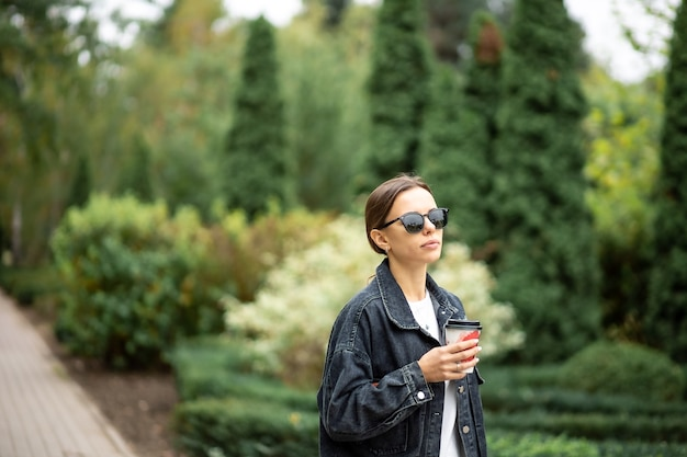Mulher jovem de óculos escuros e com um copo de papel de café no parque