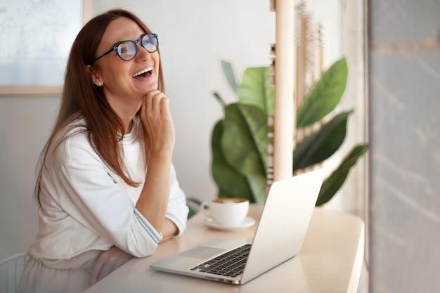 Mulher jovem de óculos rindo enquanto conversa on-line no computador durante o intervalo para o café no café