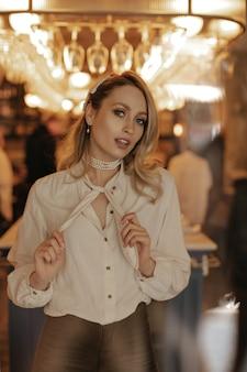 Mulher jovem de olhos cinzentos e blusa branca olha para a câmera. elegante senhora loira com camisa clara, calça escura e colar de pérolas posa em restaurante