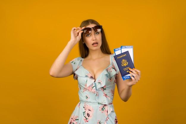 Mulher jovem de olhos saltados em um vestido azul com flores e óculos de sol está segurando as passagens aéreas com um passaporte com fundo amarelo. alegra-se com a retomada do turismo após a pandemia do coronovírus.