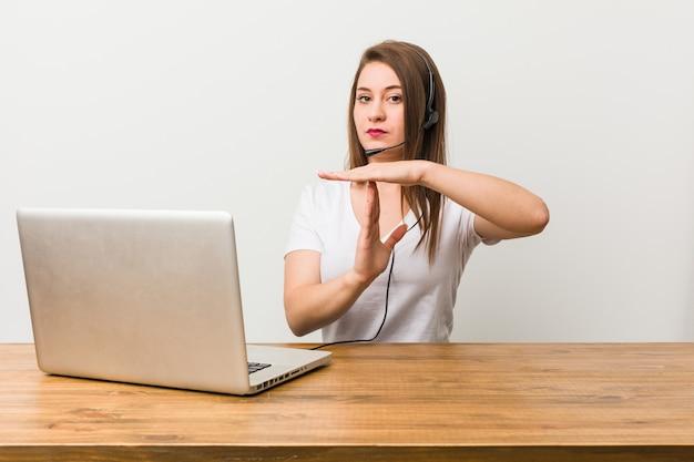 Mulher jovem de operador de telemarketing mostrando um gesto de tempo limite.