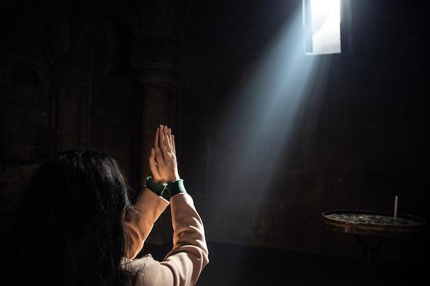 Mulher jovem de oração à luz da igreja.