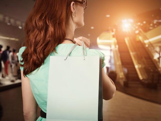 Mulher jovem de pé atrás com uma sacola no shopping