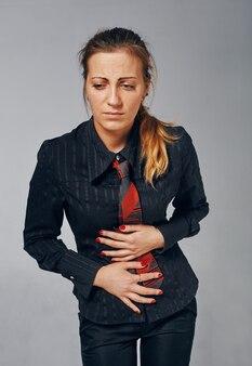 Mulher jovem, de pé, segurando a barriga como se estivesse doente ou desconfortável