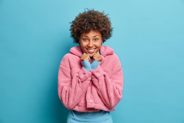 Mulher jovem de pele escura e satisfeita com um sorriso amável e com as mãos embaixo do queixo