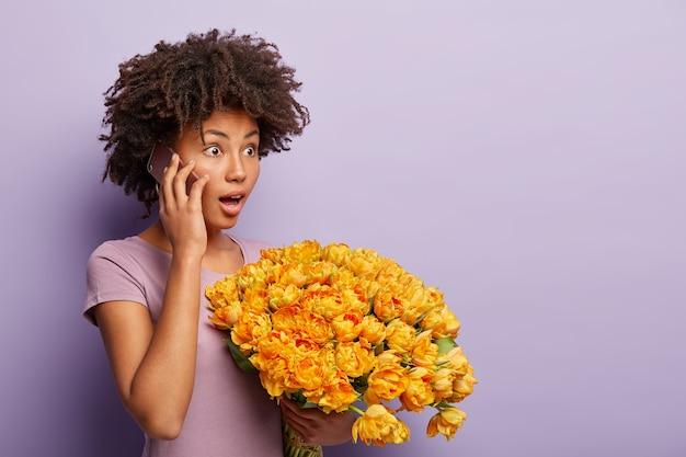 Mulher jovem de pele escura emocional conversa ao telefone, impressionada com notícias chocantes, segura o celular perto do ouvido, obtém tulipas amarelas aromáticas, posa sobre a parede roxa, copia o espaço no lado direito