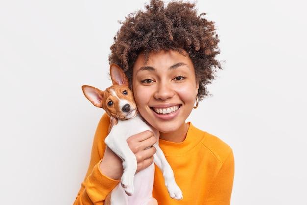 Mulher jovem de pele escura feliz expressa cuidado e responsabilidade para com seu cachorrinho favorito, obtém prazer enquanto brinca com sorrisos de cachorro amplamente se divertem juntos isolados sobre uma parede branca