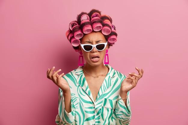 Mulher jovem de pele escura frustrada, de mau humor, expressa emoções negativas, levanta as mãos com decepção, sente-se entediada e solitária, usa óculos escuros da moda e rolos de cabelo na cabeça