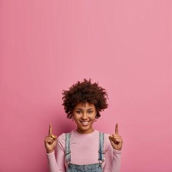 Mulher jovem de pele escura positiva aponta o dedo indicador para cima