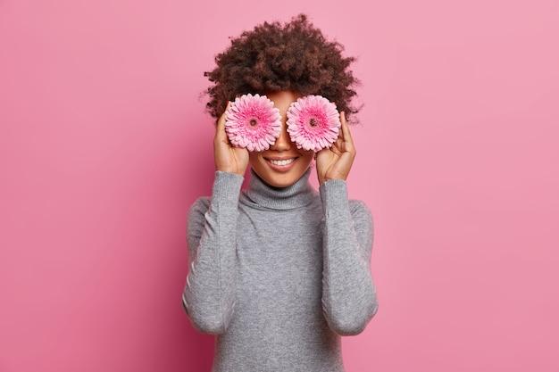 Mulher jovem de pele escura positiva gosta do dia de primavera, segurando flores de gerbera rosa nos olhos