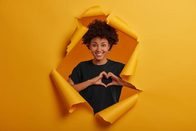 Mulher jovem de pele escura satisfeita mostra o símbolo do coração, forma o sinal do amor com as mãos, sorri feliz, usa camiseta preta e brincos