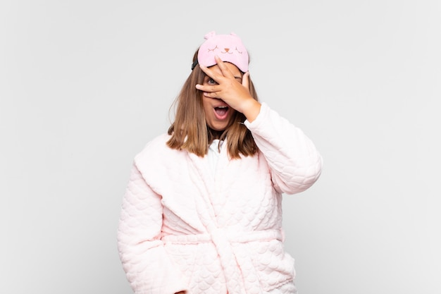 Mulher jovem de pijama, parecendo chocada, assustada ou apavorada, cobrindo o rosto com a mão e espiando por entre os dedos