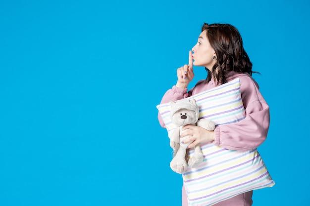 Mulher jovem de pijama rosa conversando com alguém na cama azul de insônia noite pesadelo festa descanso sono