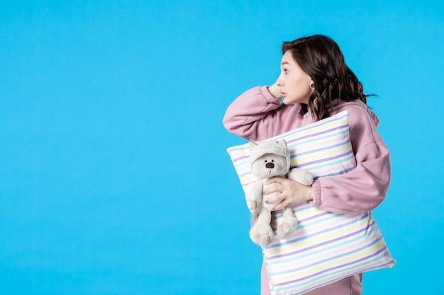 Mulher jovem de pijama rosa conversando com alguém na cama azul de insônia, noite, pesadelo, sonho, festa, vista frontal, dormir