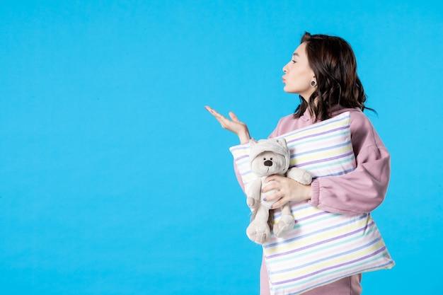 Mulher jovem de pijama rosa conversando com alguém na cama azul insônia, noite, pesadelo, sonho, festa, descanso, vista frontal