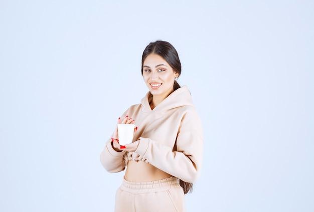 Mulher jovem de pijama rosa segurando um copo de bebida