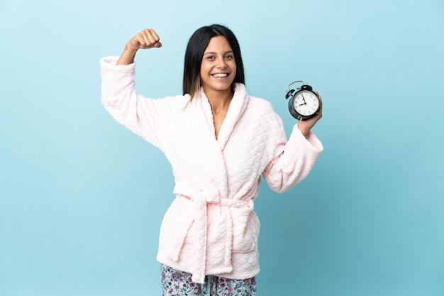 Mulher jovem de pijama sobre uma parede isolada de pijama e segurando o relógio enquanto faz um gesto forte
